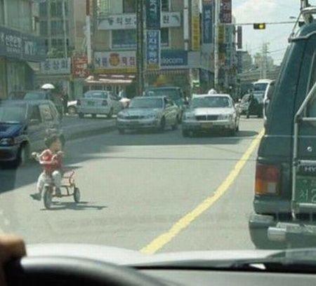 niño en triciclo por la carretera