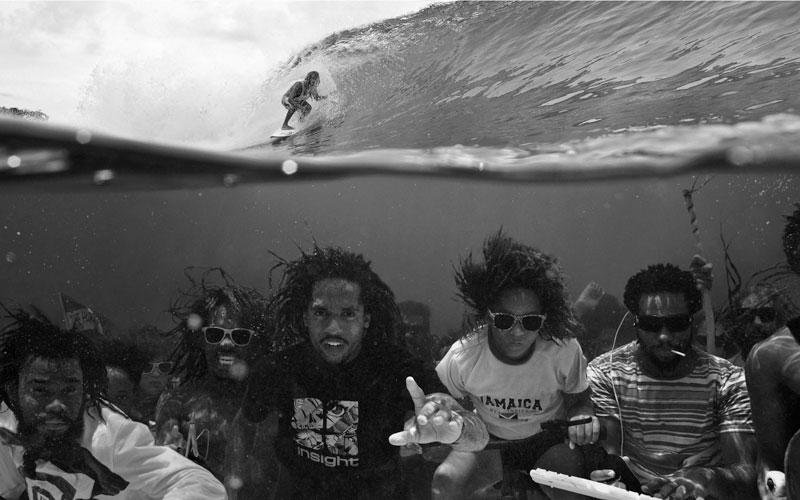 negros afro bajo el agua y un surfista en la superficie