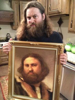 tipo con barba enseñando cuadro antiguo con su doble