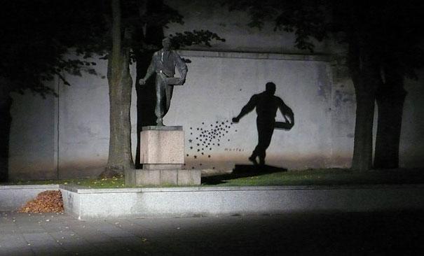 Estatua sombra con estrellas pintadas en la pared