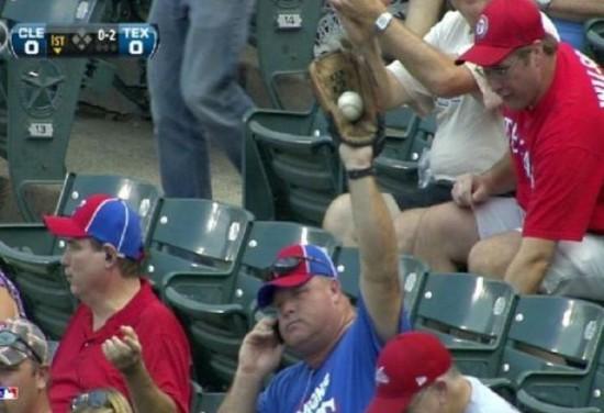 partido de beisbol, sentado hablando con el movil y coge la pelota