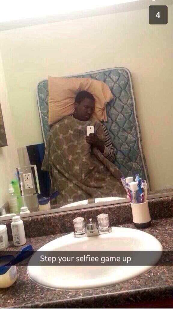 selfie negro con colchon, manta y almohada contra la pared