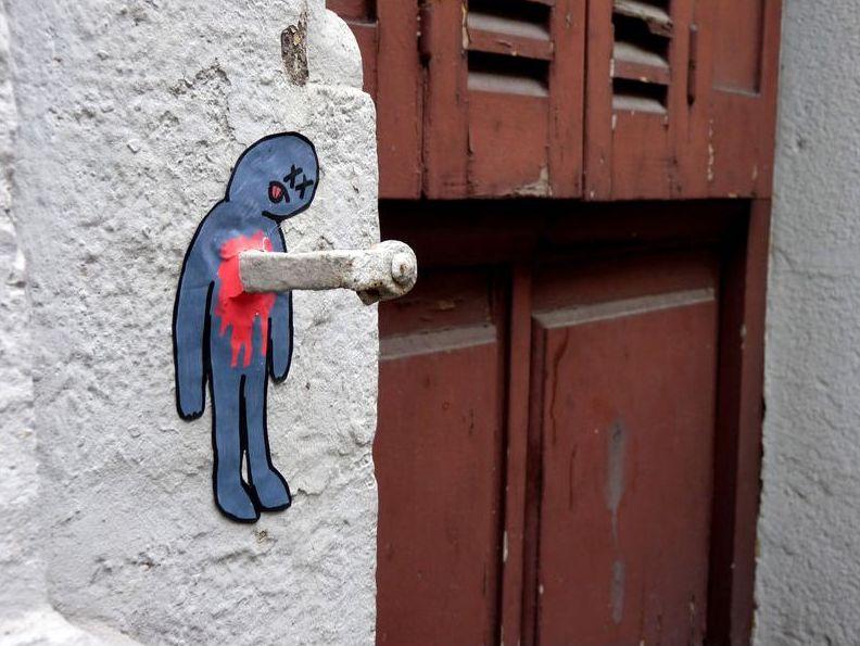 arte urbano dibujo de figura con gancho clavado