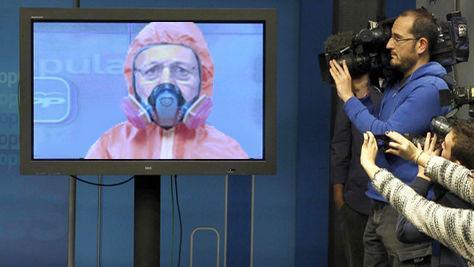 mariano rajoy rueda de prensa en pantalla y con traje de proteccion ebola