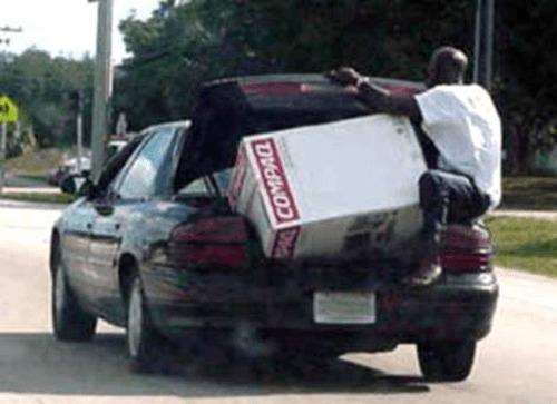 coche caja enorme en maletero y hombre sujetandola