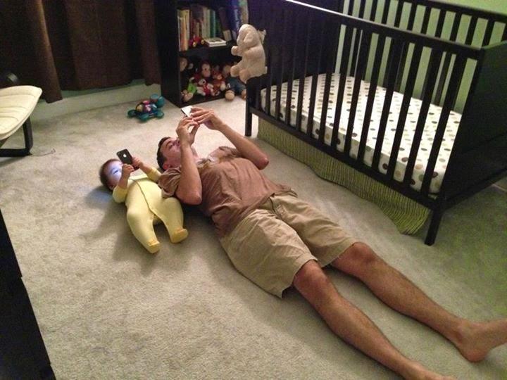 padre y bebe tumbados mirando el movil