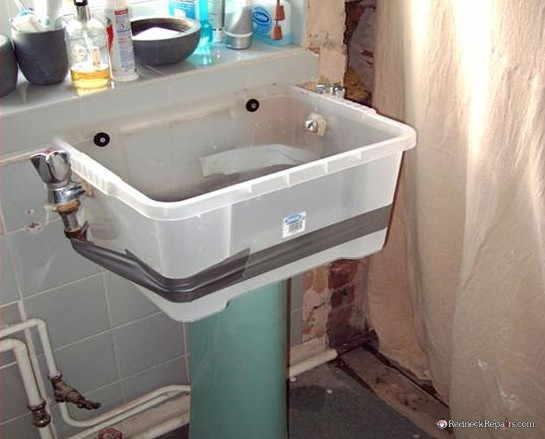 lavabo cutre con cubo de plastico