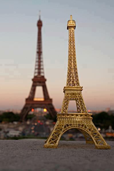 foto curiosa torre eiffel en miniatura con la torre eiffel de fondo