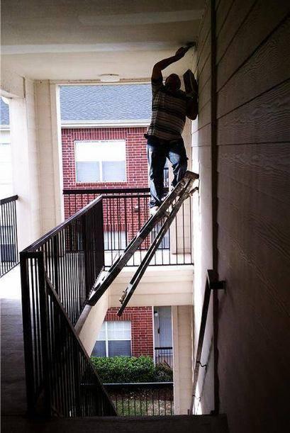 albañil pintando encima de una escalera apoyada en el rellano