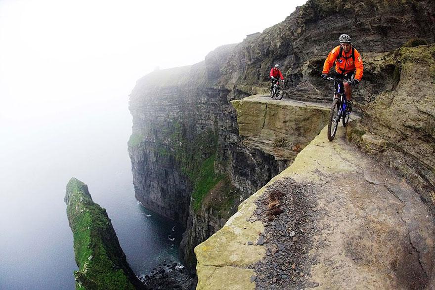 ciclistas por el borde de un acantilado