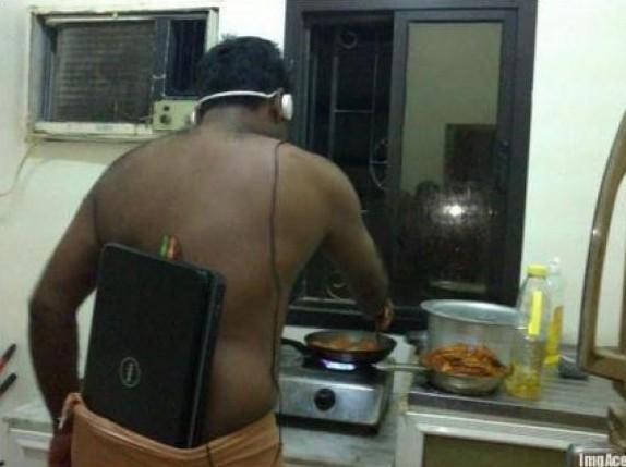 escuchando auriculares con el portatil a cuestas mientas cocina
