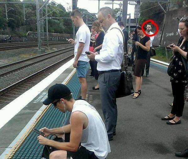 estacion de tren todos mirando el movil menos uno
