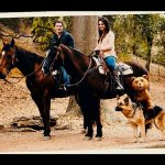 Pareja a caballo y acompañante