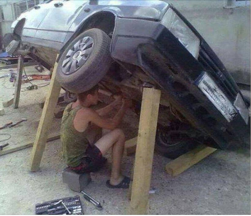 mecanico arreglando coche con tablas