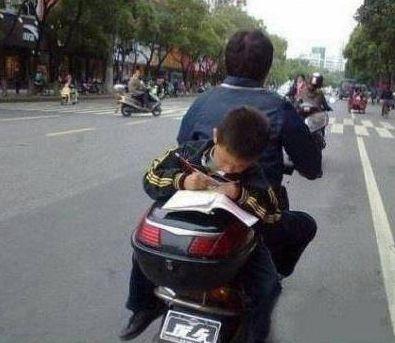 nino en asiento trasero de moto haciendo los deberes