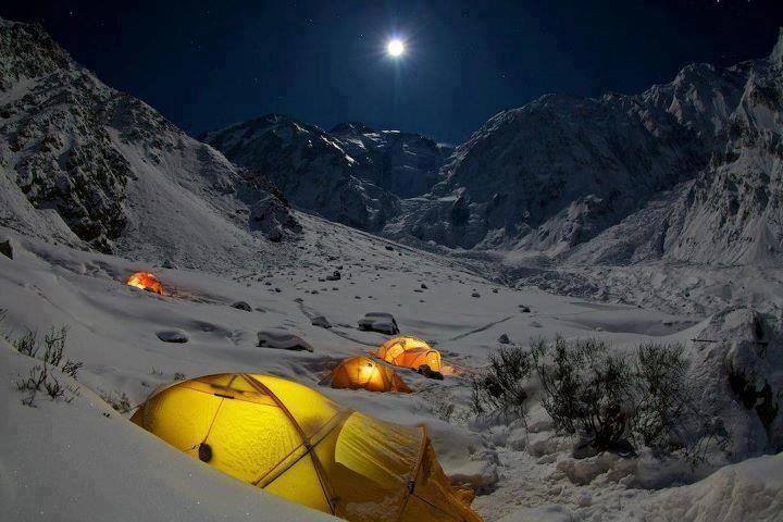 Tiendas de campaña por la noche en montaña nevada