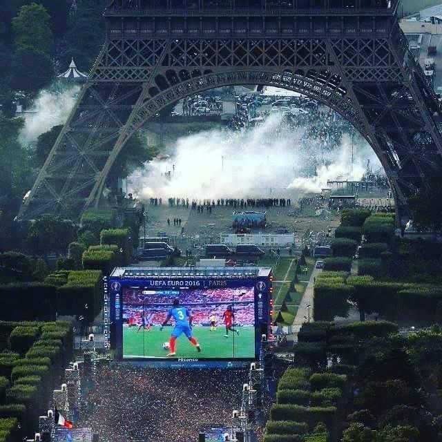 partido de futbol en pantalla y disturbios bajo la torre eiffel