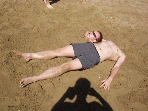 tumbado en la arena con la cabeza en la mano